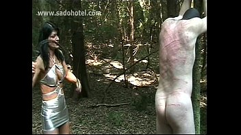 slave naked girl band tied on a tree gets hits with a whip by horny mistress